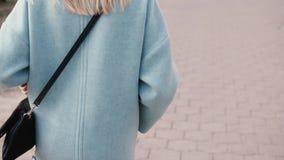 Het achtermeisje die van het meningsblonde modieuze kleren dragen Glamourvrouw die in de straat lopen De manierindustrie steadica stock video