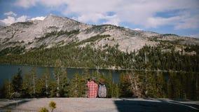 Het achtermenings gelukkige romantische paar zit samen bij het epische panorama die van het bergmeer selfie bij Yosemite-park lan stock videobeelden
