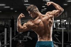 Het achtermenings spiermens stellen in gymnastiek, terug en bicepsen die tonen Sterk mannelijk naakt torso, het uitwerken royalty-vrije stock foto
