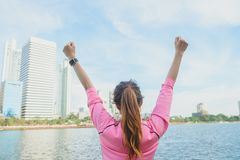 Het achterschot van jonge Aziatische vrouw ontspant zich en verwarmt neer na stads lopende oefening met een achtergrond van de st Stock Foto