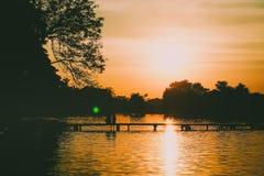 Het achtersilhouet van een paarzitting op de brugholding overhandigt mooi bosmeer bij zonsondergangachtergrond royalty-vrije stock foto's