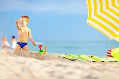 Het actieve jong geitje spelen in zand op het strand Stock Foto