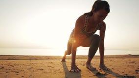 Het actieve jonge vrouw streching en het praktizeren yoga op strand bij zonsondergang stock videobeelden