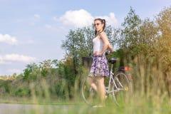 Het actieve Leven Een vrouw met een fiets geniet van de mening bij de zomer bosfiets en ecologieconcept stock foto