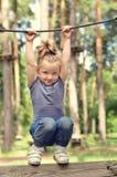 Het actieve meisje hangen op een kabel in het park Stock Foto