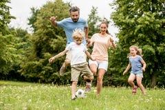 Het actieve voetbal van het familiespel stock afbeeldingen