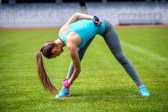 Het actieve vrouwelijke agent uitrekken en het ontspannen spieren zich na harde training Fitness en sportenconcept Royalty-vrije Stock Foto