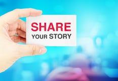 Het adreskaartje van de handholding met aandeel uw verhaal met onduidelijk beeldblauw Stock Foto