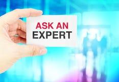 Het adreskaartje van de handholding met Ask een deskundige met onduidelijk beeld blauwe bok Royalty-vrije Stock Foto's