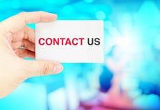 Het adreskaartje van de handholding met contact ons met onduidelijk beeld blauwe bokeh Stock Afbeeldingen