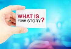 Het adreskaartje van de handholding met wat uw verhaal is? met onduidelijk beeldbl Royalty-vrije Stock Fotografie