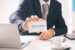 Het adreskaartje van de zakenmanholding met succestekst op het wordt geschreven die royalty-vrije stock afbeelding