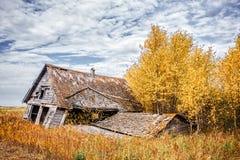 Het afbrokkelende huis van het land in de herfstlandschap Stock Afbeelding