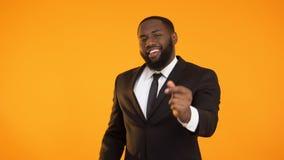 Het afrikaans-Amerikaanse mannetje is formeel kostuum makend het dansen bewegingen, reclame stock videobeelden