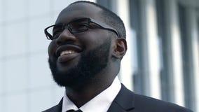 Het Afrikaanse Amerikaanse bedrijfsmens glimlachen, die rooskleurige toekomst, succes onderzoeken stock footage