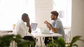 Het Afrikaanse Amerikaanse en Kaukasische jonge zakenlieden spreken die op het werk lachen stock footage
