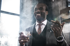 Het Afrikaanse Amerikaanse glas van de zakenmanholding met whisky en rokende sigaar royalty-vrije stock fotografie