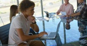 Het Afrikaanse Amerikaanse mannelijke uitvoerende werken aan laptop in een modern bureau 4k stock videobeelden