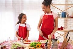 Het Afrikaanse Amerikaanse moeder en dochter voorbereidingen treffen stock afbeeldingen