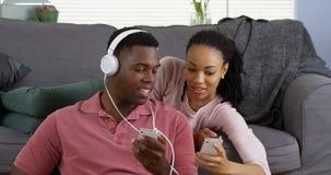 Het Afrikaanse Amerikaanse paar luistert aan muziek en doorbladert Internet met smartphones Stock Afbeelding