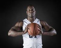 Het Afrikaanse Amerikaanse portret die van de Basketbalspeler een bal houden Stock Foto's