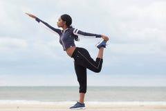 Het Afrikaanse Amerikaanse vrouw in evenwicht brengen op één been bij het strand stock fotografie