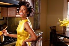 Het Afrikaanse Amerikaanse vrouw koken in de keuken Stock Foto's