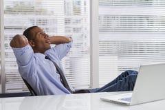 Het Afrikaanse Amerikaanse zakenman ontspannen bij horizontaal bureau, Royalty-vrije Stock Foto's