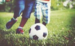 Het Afrikaanse Concept van Broerplaying football outdoors stock afbeeldingen