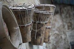 Het Afrikaanse drumsDjembe en trommelkader hing op muur buiten vakman` s workshop royalty-vrije stock foto's
