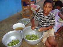 Het Afrikaanse kind koken Stock Foto's