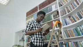 Het Afrikaanse mannelijke boek van de studentenlezing van de planken terwijl status op ladder in universitaire bibliotheek stock video