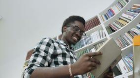 Het Afrikaanse mannelijke boek van de studentenlezing terwijl status op ladder in universitaire bibliotheek stock footage
