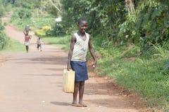 Het Afrikaanse meisje neemt waterhuis stock afbeeldingen