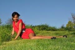 Het Afrikaanse meisje ontspannen op een gebied van groen Royalty-vrije Stock Foto's