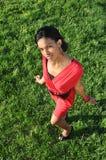 Het Afrikaanse meisje stelt met een groene grasachtergrond Stock Foto's