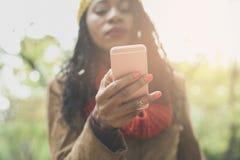 Het Afrikaanse meisje van Amerika in park die slimme telefoon met behulp van Nadruk op hand stock fotografie