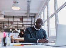 Het Afrikaanse mens schrijven neemt van terwijl het werken aan laptop nota royalty-vrije stock afbeelding