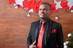 Het Afrikaanse mens stellen tegen Kerstmisachtergrond Royalty-vrije Stock Foto's