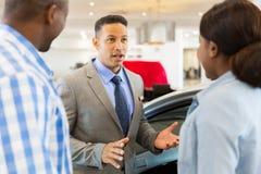 het Afrikaanse paar van de autoverkoper stock foto's