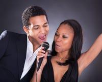 Het Afrikaanse Paar Zingen met Microfoon stock foto's