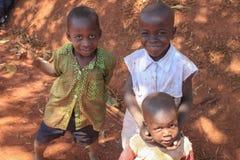 Het Afrikaanse spel van dorpskinderen dichtbij hun huizen in de Kampala voorstad royalty-vrije stock fotografie
