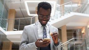 Het Afro-Amerikaanse gebaarde Zakenman dragen past en glazen die op telefoon in modern bureau texting aan Bedrijfs concept stock video