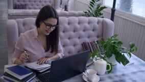 het afstandsonderwijs, glimlachende jonge vrouw schrijft nota's in notitieboekjezitting bij lijst met laptop in koffie stock video