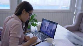 het afstandsonderwijs, het slimme online videoonderwijs van meisjes gebrilde passen voor zelfontplooiing gebruikt laptop computer stock video