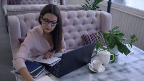 het afstandsonderwijs, vrouwelijke student met pen schrijft nota's binnen in notitieboekjezitting bij bureau met laptop stock footage
