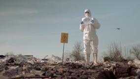 Het afval van mensenleven, vrouw in eenvormige en beschermende glazen die affiche houden denkt groene status bij stortplaats in l stock video