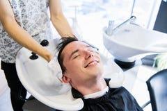 Het afvegende hoofd van de mensenkapper van een knappe glimlachende cliënt met een handdoek bij de herenkapper stock afbeelding