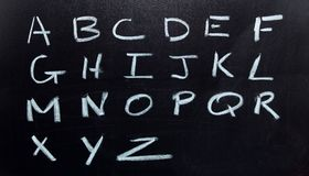 Het Alfabet, op een zwarte raad wordt getrokken die Royalty-vrije Stock Foto's