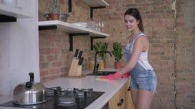 Het algemene schoonmakende huis, gelukkige meisjeshuishoudster in rubberhandschoenen voor het schoonmaken veegt stoffig meubilair stock videobeelden